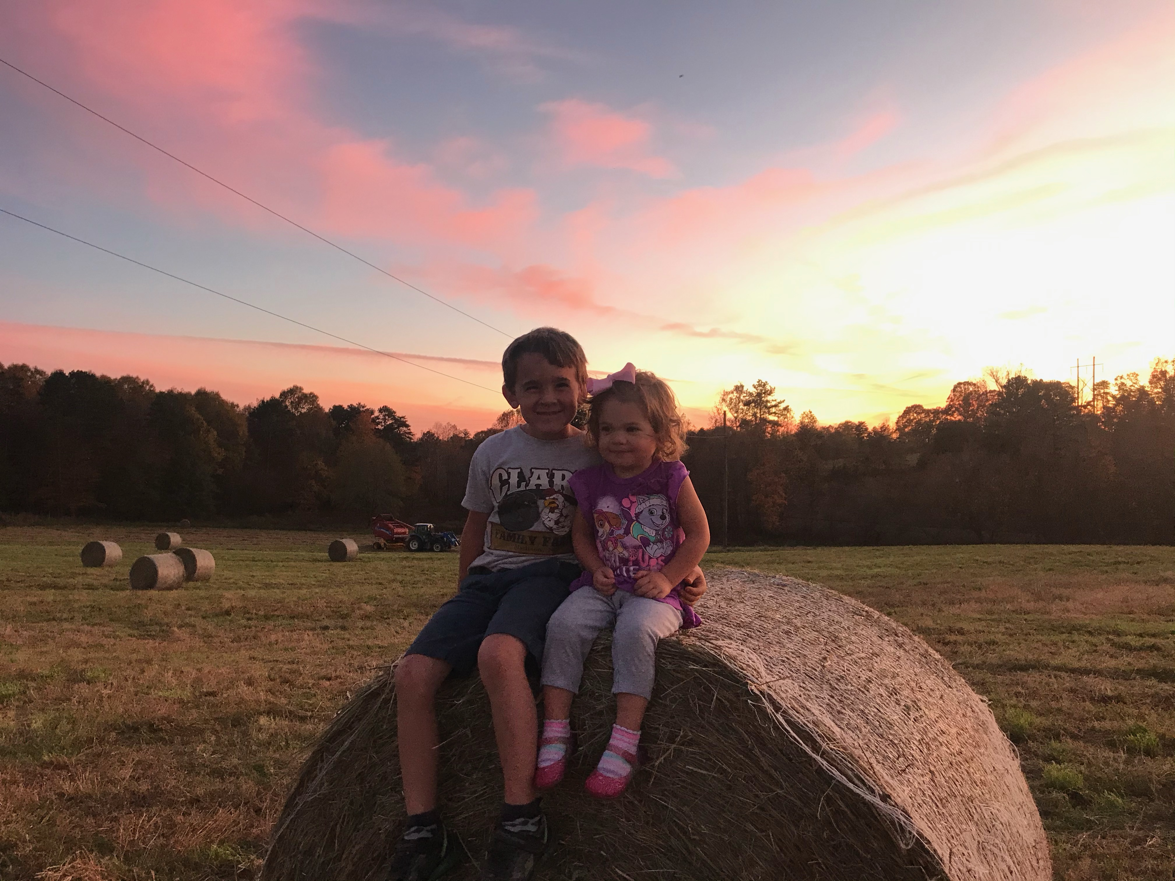 two kids on a hay bale
